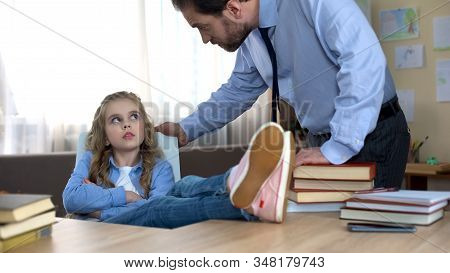 Mischievous Daughter Sitting With Legs On Table, Ignoring Fathers Remarks