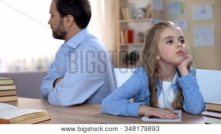 Offended Dad And Kid Sitting At Table And Keeping Silent, Conflict In Family