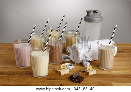 Glasses Of Various Types Of Colourful Milkshake With Paper Straws And Dieting Paraphernalia  On A Wo
