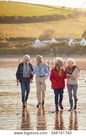 Group Of Smiling Senior Friends Walking Arm In Arm Along Shoreline Of Winter Beach