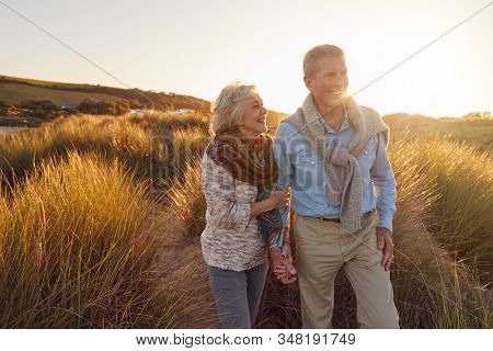 Loving Retired Couple Walking Arm In Arm Through Sand Dunes On Beach Vacation Against Flaring Sun