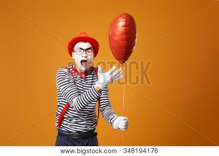 Happy clown mime in red hat and vest holds heart ball in his hands