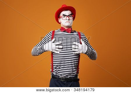 Mime man in vest and red hat on orange background