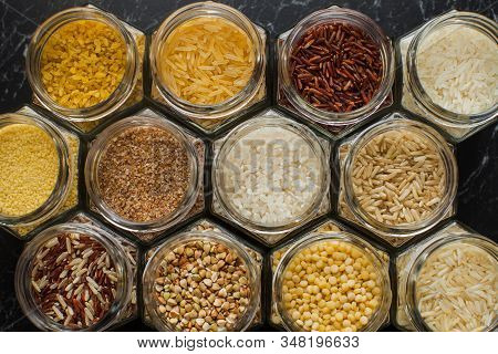 Top View Of Glass Jars With Various Cereals, Rice, Couscous, Bulgur, And Buckwheat.