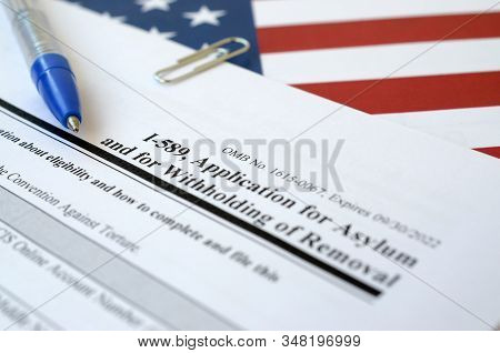 I-589 Application For Asylum And For Withholding Of Removal Blank Form Lies On United States Flag Wi