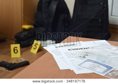 Evidence Labels And Green Card With Ssn Number Lies On Table With Big Amount Of Items As Evidence In