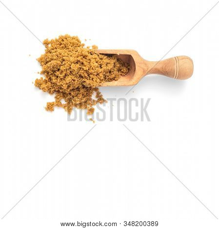 Natural unrefined brown sugar in scoop on white background