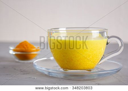 Golden Milk In A Glass Gray Cup On A Gray Background