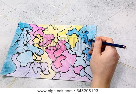 Man Draws An Abstract Imaginary Picture With A Pencil And Decorates It With Different Colors, A Psyc