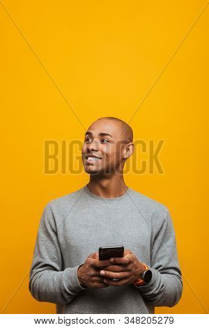 Portrait of an attractive smiling confident casual young african man standing over yellow background, using mobile phone, looking away