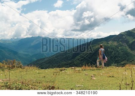 Woman In A Mountain Meadow With White Flowers