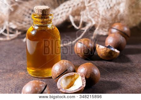Cosmetic And Medicinal Macadamia Oil, On A Brown Background, Close-up. Oil For Women, Cosmetology, T