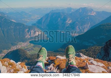Legs Of Traveler In Stylish Green Sneakers Sitting On A High Mountain Cliff Enjoying Scenery Mountai