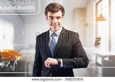 Cheerful Young Businessman With Smartwatch Standing In Blurry Office With Double Exposure Of Infogra