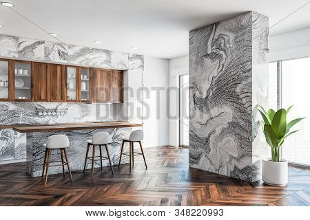 Corner Of Luxury Kitchen With Gray Marble Walls, Wooden Floor, Marble Countertops, Wooden Cupboards