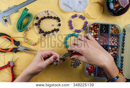 Jewelry Making. Making A Bracelet Of Colorful Beads. Female Hands With A Tool On A Yellow Background