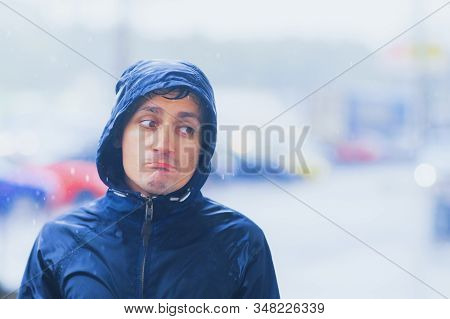 Portrait Of A Sad Man In A Raincoat And A Hood In The Rain. Bad Stormy Rainy Weather Concept.