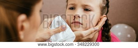 Panoramic Shot Of Mother Holding Napkin Near Upset Daughter With Nasal Bleeding