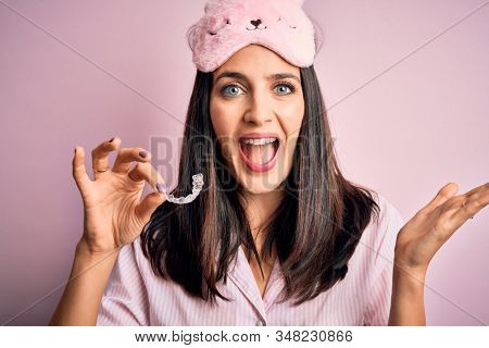 Young brunette woman with blue eyes wearing pajama holding dentist clear aligner very happy and excited, winner expression celebrating victory screaming with big smile and raised hands