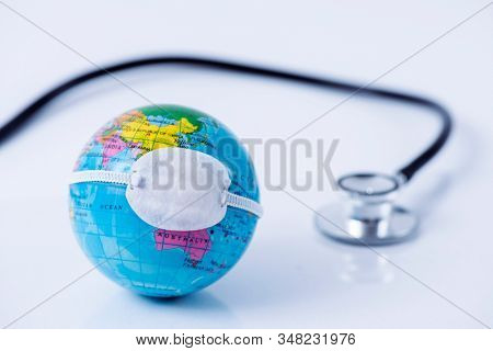 closeup of a terrestrial globe with a protective mask placed over China, depicting the recent coronavirus outbreak, next to a stethoscope