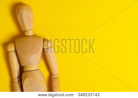 Wooden Human mannequin on a bright yellow background