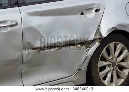 A Large Long Scratch With A Black Hole And A Dent On The Door Of A Gray Passenger Car