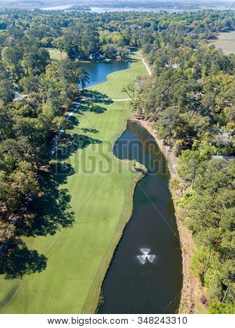 Aerial view of golf course fairway with water hazards.