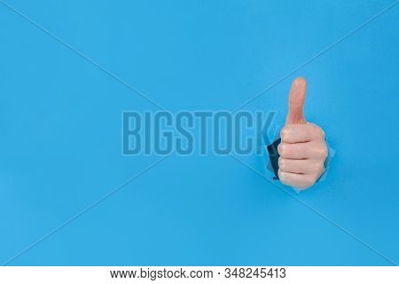 Thumbs Up Through The Hole Symbolic Approval Gesture Thumbs Up In Torn Blue Paper Sheet. Winners Han