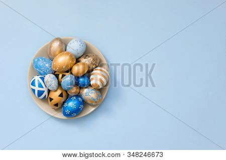 Stylish Easter Golden Decorated Eggs On Grey Plate Isolated On Blue Background. Trendy Flat Lay East