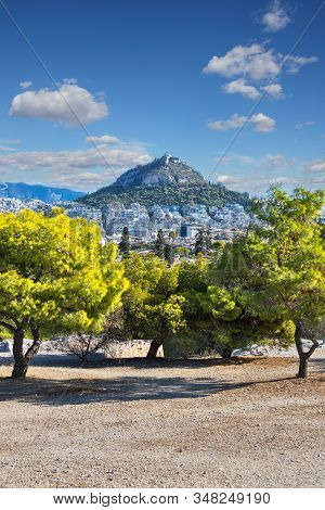 Lycabettus Hill Seen From Filopappou Hill In Athens Greece, On A Blue Sky With Clouds