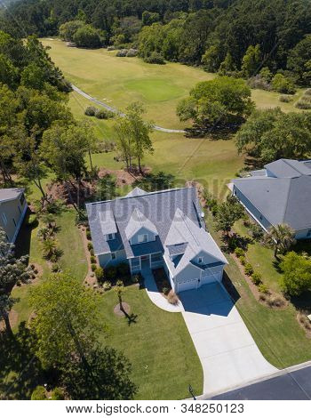 Aerial view of new home on beautiful wooded lot with golf course behind it.
