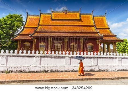 A Buddhist Monk Walks By The Wat Sen Temple In Luang Prabang, Laos.