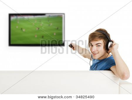 Young man sitting on the couch using a remote control and watching a football game on tv
