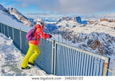 Woman Skier Taking A Break And Enjoying The Mountain Views Towards Sassolungo And Sella Group In Dol