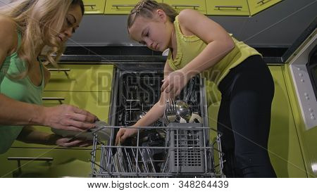 Mother Teaching Daughter Smart Girl Learning To Use Dishwasher. Young Mistress Children Loading Putt