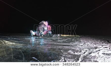 Young Loving Couple Skating At Ice Rink At Night. Man And Woman Kiss Hug Have Fun Learn To Skate. Ma
