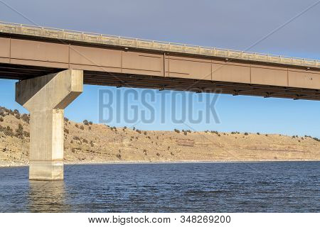 Beam Bridge With Abutment Foundation Against Rugged Land And Cloudy Sky