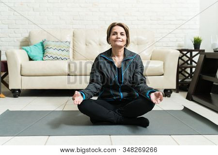 Full Length Of Smiling Elderly Woman Practicing Yoga On Exercise Mat At Home