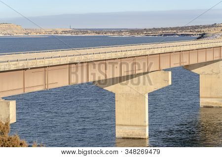 Stringer Bridge With Scenic View Of Blue Water And Snowy Terrain In Winter