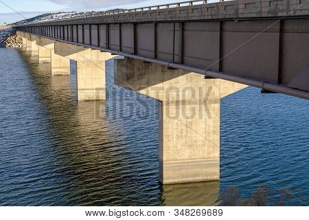 Deck Of A Beam Bridge Supported By Abutments Or Piers Spanning Over Blue Water