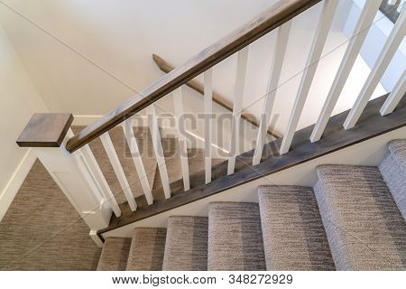 U Shaped Indoor Staircase Of Home With Treads And Landing Covered With Carpet