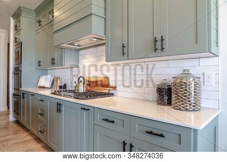 Kitchen Interior With Cooktop On White Counter Top Under Hanging Cabinets