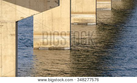 Panorama Views Underneath A Beam Bridge With Abutments Against The Sunlit Lake Water