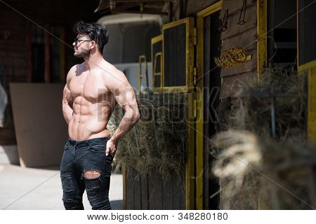 Handsome Cowboy Man Standing Strong And Posing At Ranch Outdoors Wearing Black Jeans