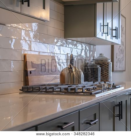 Photo Square Frame Kitchen Work Area With Cabinets Cooktop Countertop And Tile Backsplash