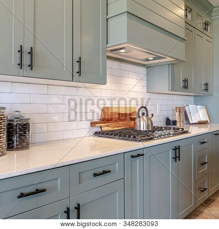 Square Frame Kitchen Interior With Cooktop On White Counter Top Under Hanging Cabinets