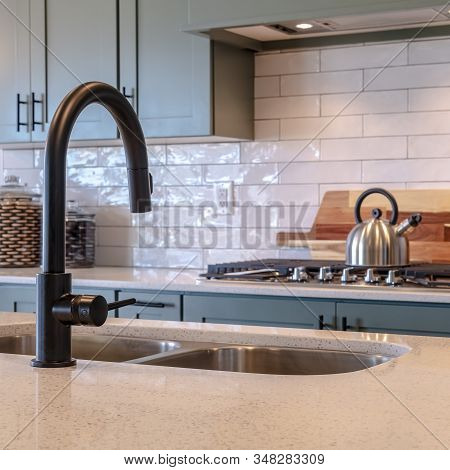 Photo Square Black Faucet And Double Bowl Kitchen Island Sink Against Cooktop And Cabinets