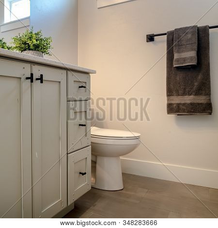 Square Toilet And Vanity Cabinet Inside Bathroom With White Wall Brown Floor And Window