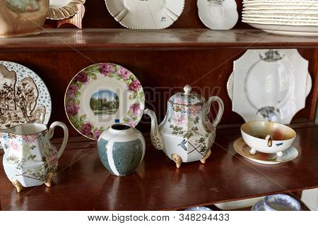 Vintage Cabinet With Decorative Porcelain Dishes For Sale At An Antique Store. Maine, Usa