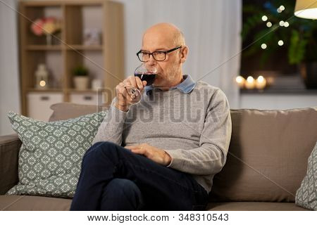 people, alcohol and drinks concept - senior man drinking red wine from glass at home in evening